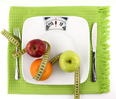 Diet concept. Fruits with measuring tape  on a plate like weight scale