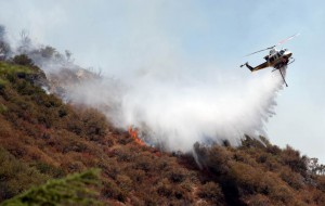 A chopper trying to distinguish the widely spread forest fire.