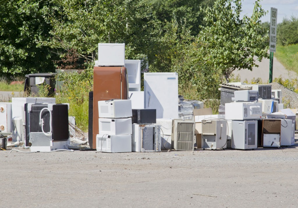 A stack of old appliances such as refrigerators freezers and air conditioners stacked up in a pile at a recycling garbage dump.